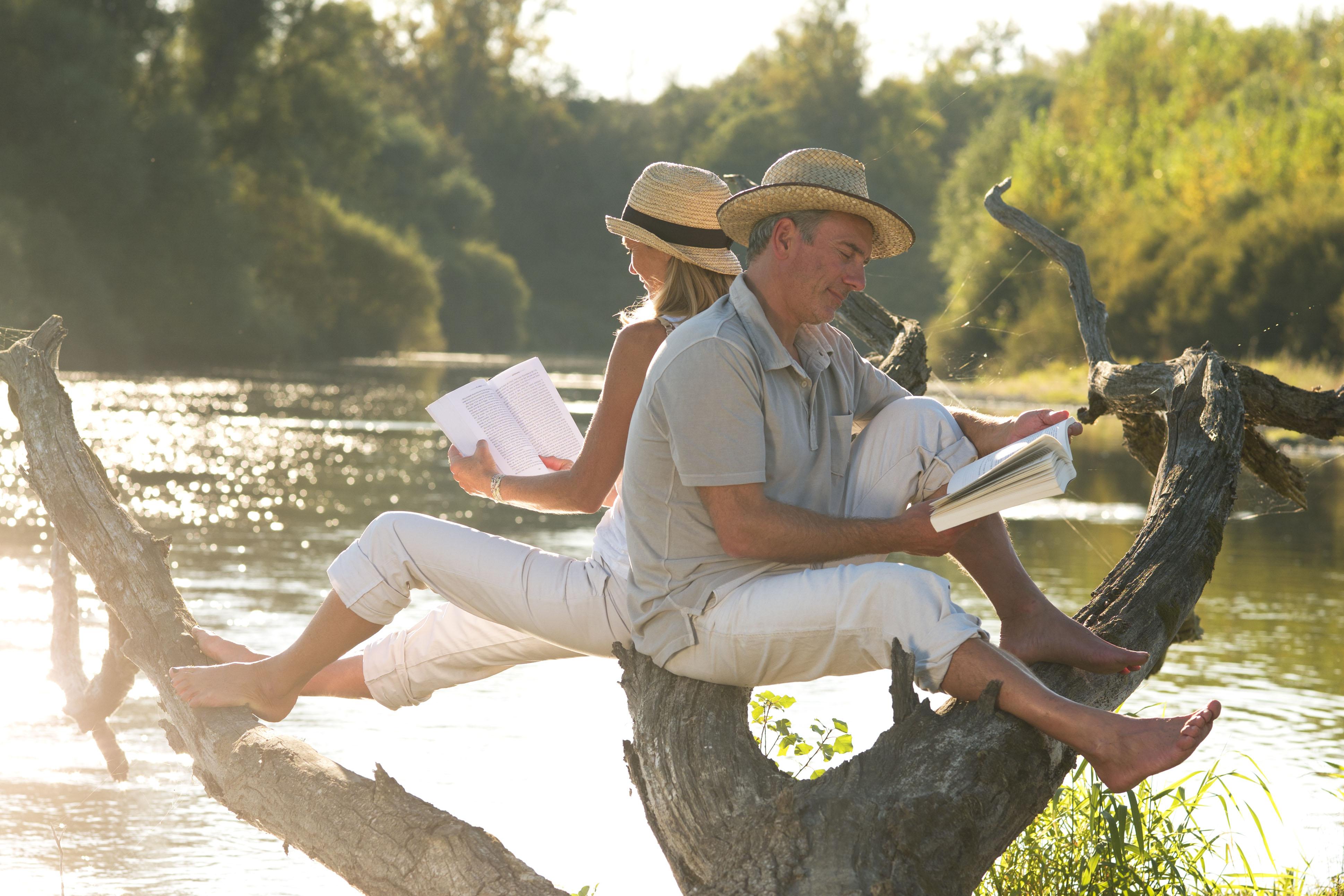 Couple lisant au bord de l'eau